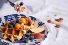 To eat waffle. Closeup of a fork cutting a piece of blueberry waffle decorated with fresh blueberry in a nice dish Royalty Free Stock Photo