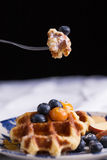 To eat waffle. Closeup of a fork cutting a piece of blueberry waffle decorated with fresh blueberry in a nice dish Stock Photo