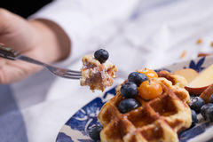 To eat waffle. Closeup of a fork cutting a piece of blueberry waffle decorated with fresh blueberry in a nice dish Stock Image