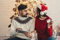 This is to expensive! Young couple using credit card and shoppin. G online at home. Buying Christmas presents Stock Photo