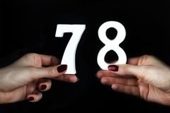 To female hands the figure of seventy-eight. On a black background, female hand with numbers seventy-eight Royalty Free Stock Image