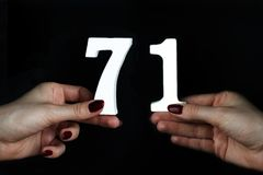 To female hands the figure of seventy-one. On a black background, female hand with numbers seventy-one Royalty Free Stock Photo