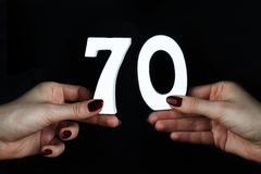 To female hands the number seventy. On a black background, female hand with the number seventy Royalty Free Stock Photos
