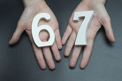 To female hands the number sixty-seven. On a black background, female hand with number sixty-seven Royalty Free Stock Image