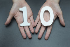 To female hands the number ten. On a black background, female hand with number ten Stock Images
