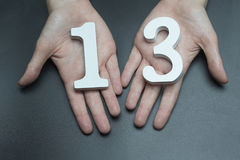 To female hands the number thirteen. On a black background, female hand with number thirteen Royalty Free Stock Images