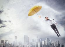 To fly high. Businessman flying with an umbrella over city Stock Photo