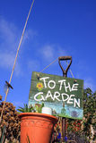 To The Garden 3. A portrait format image set at a low angle, of a terracotta coloured flower pot set in frot of a garden fork with a hand painted sign with Royalty Free Stock Images