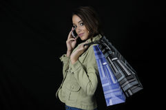 To go shopping. Side view of woman holding shopping bags against black background royalty free stock photos