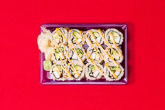 To go sushi box on red table cloth with wasabi ginger Royalty Free Stock Photos