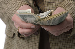 To have money to burn. Money makes money. The man in a checkered jacket recalculates money stock photo