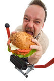 To hell with exercises. Man eating big hamburger on top of trainer device - isolated Royalty Free Stock Image