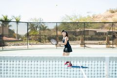 About to hit a winning shot. Beautiful young female tennis player aligning herself to hit a winning shot on tennis court Stock Photo