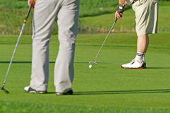 To the hole. Golfer hitting ball to the hole on golf course Stock Photography
