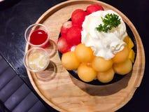 To jest mieszanka owocowy Bingsu łączący z mango, kantalupem i arbuzem w czarnej filiżance który jest lodowymi płatek śniegu, ? fotografia stock