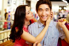 About to kiss. Girl being about to kiss her boyfriend smiling at cam, shopping series Stock Photography