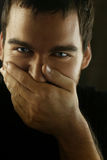 About to laugh. Portrait of man covering face with hand about to laugh Royalty Free Stock Photo