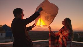 To launch a sky lantern at night on the roof. The lovers are together. Chinese sky lanterns
