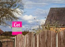 To let sign. Outside house on fence with blue sky background Stock Image