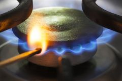 To light a natural gas burner with a match. To light a blue flame natural gas burner with a match in the Netherlands royalty free stock photography