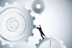 To make business work concept with businessman spinning gears Royalty Free Stock Photo