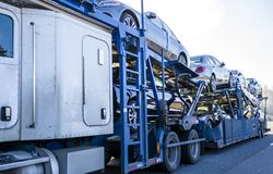 White big rig car hauler long distance semi truck transporting cars on two level semi trailer on the straight road. To meet the people need for passenger cars stock photography