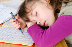 To much Homeworks. Little girl sleeping over homeworks Royalty Free Stock Images