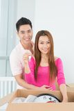 To a new house!. Vertical portrait of a young couple with a key from a new house Royalty Free Stock Photos