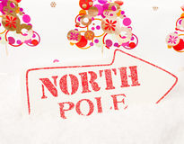 To The North Pole. A white sign showing the way to the north pole sat in snow Stock Photography