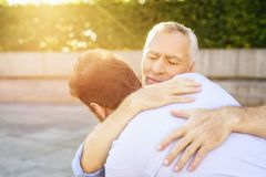 To the old man who sits in the park on a wheelchair came his son. He is hugging the old man royalty free stock photos