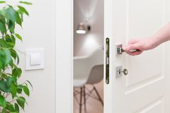 To open the door. Modern white door with chrome metal handle and a man`s arm. Elements of interior closeup Royalty Free Stock Photography