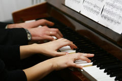 To play on a piano in four hands Royalty Free Stock Photo