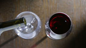 To pour two glasses of red wine. top view. Male and female hands stock footage