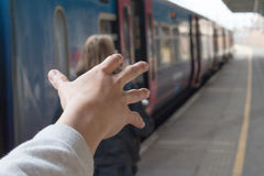 To reach the person leaving. Hand trying to reach the person leaving him in the Train Station Stock Images