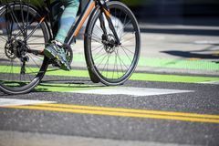 Woman in leggings traveling through the city on bicycle crosses the road at pedestrian crossing royalty free stock photo
