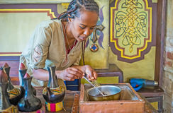 To roast the coffee beans. KIEV, UKRAINE - JUNE 4, 2017: The interesting process of hand roasting coffee beans for traditional Ethiopian coffee ceremony is Royalty Free Stock Images