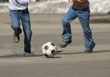To run behind a ball. Children on the city area play football Stock Photography