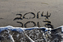 2013 to 2014 in the Sand. A picture 2013 going to 2014 in the Sand drawn in the sand with 2013 being washed out stock images