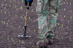 To seek treasures on earth with a metal detector. Man to seek treasure on earth with a metal detector, walks the field, squeak gold Stock Photography