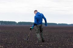 To seek treasures on earth with a metal detector royalty free stock image