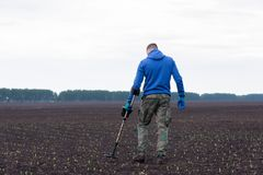 To seek treasures on earth with a metal detector. Man to seek treasure on earth with a metal detector, walks the field, squeak gold Royalty Free Stock Photo