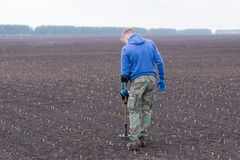 To seek treasures on earth with a metal detector. Man to seek treasure on earth with a metal detector, walks the field, squeak gold Royalty Free Stock Images