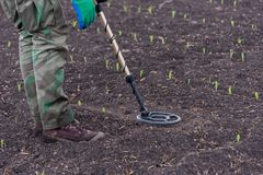 To seek treasures on earth with a metal detector. Man to seek treasure on earth with a metal detector, walks the field, squeak gold Stock Photo