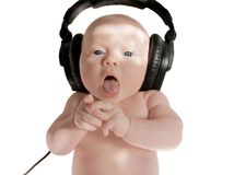 To sing. Baby girl sings in big black headphones, on white background Royalty Free Stock Images