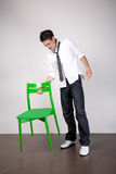 About to sit. Young man with green chair  preparing to sit for an interview Royalty Free Stock Photography