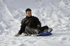 Hispanic teenager ending his slide on a winter day Royalty Free Stock Images