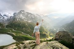 To the sun, swiss alps. Happy woman resting in spring swiss Alps, sustenpass 2224  m Stock Photo