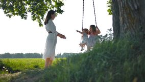 To swing on a swing is great. Two daughters rejoice, having fun and laugh out loud from the fact, that their mother is swinging on a rope swing suspended from stock footage