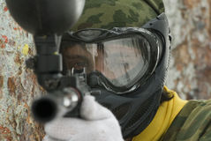 To take aim in enemy. Player in paintball prepare for fight Stock Images