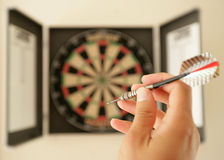 About to throw a dart. At dartboard Stock Image